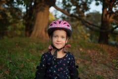 Retrato de una niña sonriente - patinador del rodillo en un casco y cojines de codo fotografía de archivo libre de regalías