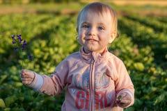 Retrato de una niña sonriente que se coloca en el jardín imagen de archivo