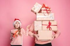 Retrato de una niña sorprendida con su padre que lleva a cabo un regalo de Navidad imagen de archivo