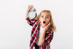 Retrato de una niña sorprendida que muestra el despertador Fotografía de archivo