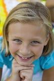 Retrato de una niña que sonríe con las manos en la barbilla Imagenes de archivo