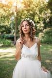 Retrato de una novia atractiva joven hermosa de la muchacha con las flores en su mirada del pelo atractiva en un vestido blanco foto de archivo libre de regalías