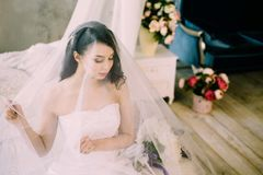 Retrato de una novia blanda atractiva hermosa con el pelo negro u oscuro largo por la mañana en casa que se sienta en cama clásic foto de archivo libre de regalías