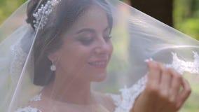 Retrato de una novia feliz en un velo con una cabeza cubierta en un parque del verano almacen de metraje de vídeo