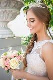 Retrato de una novia hermosa, ramo de una novia y una diadema Foto de archivo