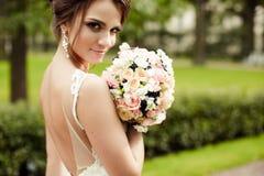 Retrato de una novia morena feliz hermosa en casarse el vestido blanco que lleva a cabo las manos en el ramo de flores al aire li Imagen de archivo