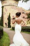 Retrato de una novia morena feliz hermosa en casarse el vestido blanco que lleva a cabo las manos en el ramo de flores al aire li Foto de archivo libre de regalías