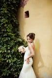 Retrato de una novia morena feliz hermosa en casarse el vestido blanco que lleva a cabo las manos en el ramo de flores al aire li Imagen de archivo libre de regalías