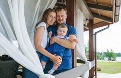 Retrato de una pareja atractiva de los jóvenes y de su hijo del bebé que se colocan en un balcón de la casa Fotos de archivo libres de regalías