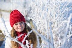 Retrato de una pequeña muchacha adorable en sombrero del invierno en bosque de la nieve Imagen de archivo