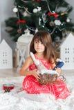 Retrato de una pequeña muchacha morena linda que sostiene un conejito del juguete en a Fotos de archivo
