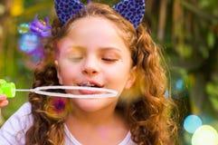 Retrato de una pequeña muchacha rizada feliz que juega con las burbujas de jabón en una naturaleza del verano, el llevar oídos az Imagen de archivo