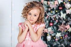 Retrato de una pequeña muchacha rubia con los rizos cerca de un árbol con las linternas y las banderas brillantemente coloreadas Imagen de archivo