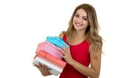 Retrato de una pila bonita sonriente de la tenencia de la muchacha de cajas de regalo aisladas sobre el fondo blanco fotos de archivo libres de regalías