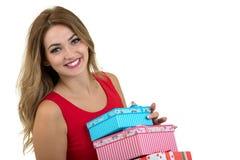 Retrato de una pila bonita sonriente de la tenencia de la muchacha de cajas de regalo aisladas sobre el fondo blanco imagen de archivo libre de regalías