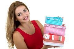 Retrato de una pila bonita sonriente de la tenencia de la muchacha de cajas de regalo aisladas sobre el fondo blanco fotos de archivo