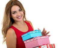 Retrato de una pila bonita sonriente de la tenencia de la muchacha de cajas de regalo aisladas sobre el fondo blanco fotografía de archivo