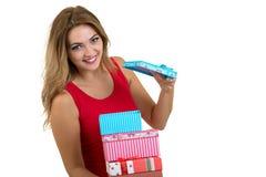 Retrato de una pila bonita sonriente de la tenencia de la muchacha de cajas de regalo aisladas sobre el fondo blanco imagen de archivo