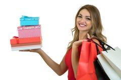 Retrato de una pila bonita sonriente de la tenencia de la muchacha de cajas de regalo aisladas sobre el fondo blanco foto de archivo