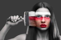 Retrato de una pintura de la mujer con un cepillo en su cara imagen de archivo libre de regalías