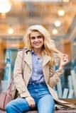 Retrato de una presentación modelo rubia feliz asombrosa mientras que se sienta en un travesaño de la tienda en un día caliente d Fotografía de archivo libre de regalías