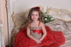 Retrato de una princesa de la niña en sentarse rojo del vestido y del sombrero fotos de archivo