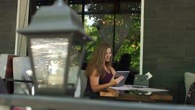 Retrato de una señora gorda del negocio en un restaurante con una tableta almacen de metraje de vídeo