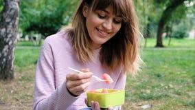 Retrato de una señora hermosa joven que come una sandía Adolescente sonriente sano con el cuenco de ensalada y de bifurcación pes almacen de video