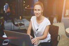 Retrato de una señora hermosa que se sienta en la tabla de café de la acera con el ordenador portátil abierto imagen de archivo
