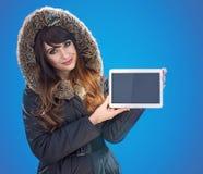 Retrato de una señora morena hermosa que sostiene una tableta vacía foto de archivo