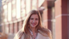 Retrato de una señora rubia agradable joven que sonríe a la cámara que toca su pelo mientras que despierta en el centro de ciudad
