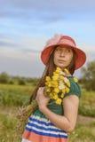 Retrato de una situación femenina joven en el campo que sostiene las flores que llevan el sombrero rojo imagen de archivo