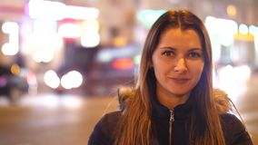 Retrato de una situación de la muchacha en una calle de la ciudad de la noche Mujer atractiva que camina a través de las calles d almacen de video