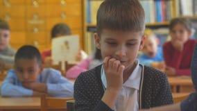 Retrato de una situación muchacho-elemental del estudiante de la escuela delante de una clase con un profesor almacen de metraje de vídeo