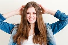 Retrato de una sonrisa feliz de la muchacha adolescente hermosa en vaqueros con las manos en la cabeza Fotos de archivo libres de regalías