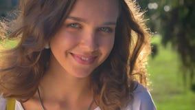 Retrato de una sonrisa joven, morenita caucásica tímida en el parque, universidad en el fondo metrajes
