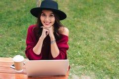 Retrato de una sonrisa muchacha bastante asiática que usa el ordenador portátil Imagenes de archivo