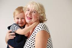Retrato de una sonrisa y una abuela feliz y su nieto Fotografía de archivo