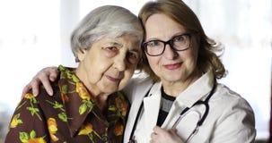 Retrato de una vieja mujer mayor con arrugas profundas y un doctor con un estetoscopio metrajes
