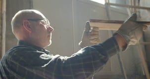 Retrato de verificações superiores do carpinteiro a qualidade de uma placa de madeira na fabricação video estoque