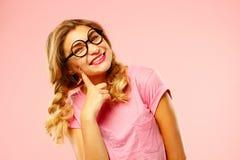 Retrato de vidros vestindo bonitos de uma estudante sobre a parte traseira do rosa Foto de Stock