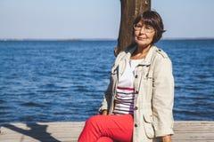 Retrato de vidros vestindo da mulher adulta no banco de rio Fotos de Stock