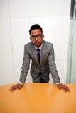 Retrato de vidros vestindo do homem de negócios indiano com mãos na tabela Fotografia de Stock Royalty Free