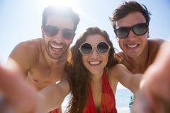 Retrato del ángulo bajo de amigos jovenes sonrientes contra el cielo claro imagen de archivo
