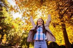 Retrato del ángulo bajo de la muchacha sonriente con los brazos aumentados mientras que se coloca en el parque Fotografía de archivo libre de regalías