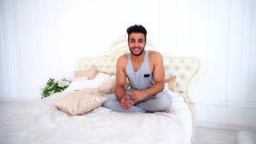 Retrato del árabe joven que descansa sobre día difícil en cama en dormitorio brillante almacen de video