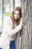 Retrato del árbol grande del abarcamiento atractivo de la muchacha. Imagen de archivo libre de regalías