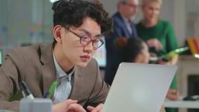 Retrato del Él-especialista asiático joven que trabaja difícilmente almacen de video
