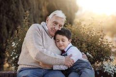 Retrato del abarcamiento del abuelo y del nieto Imagen de archivo libre de regalías