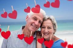 Retrato del abarcamiento mayor en la playa contra los corazones que cuelgan en una línea Fotografía de archivo libre de regalías